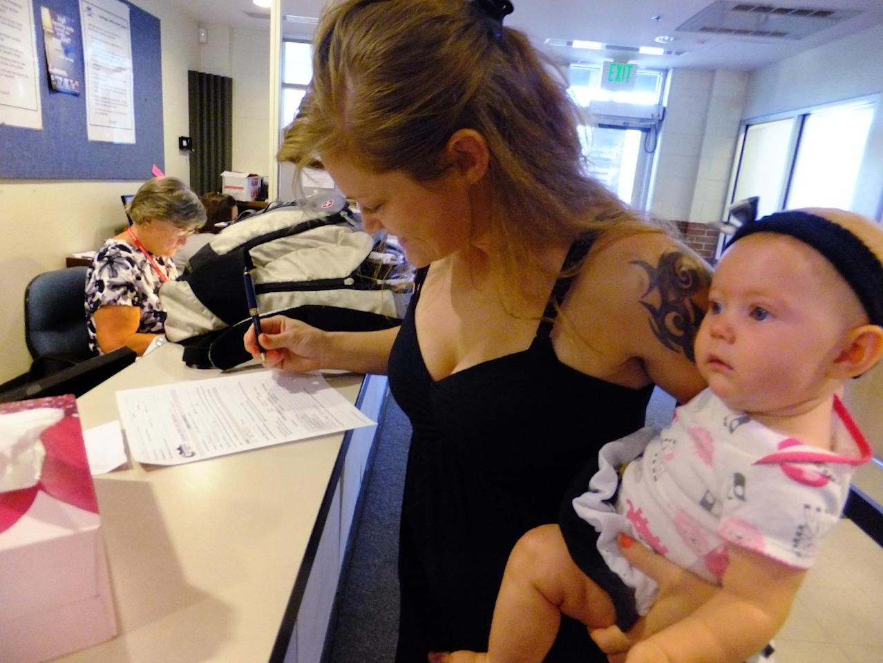 In this July 16, 2012, photo, Laura Fritz, 27, left, with her daughter Adalade Goudeseune fills out a form at the Jefferson Action Center, an assistance center in the Denver suburb of Lakewood. Both Fritz grew up in the Denver suburbs a solidly middle class family, but she and her boyfriend, who has struggled to find work, and are now relying on government assistance to cover food and $650 rent for their family. The ranks of America's poor are on track to climb to levels unseen in nearly half a century, erasing gains from the war on poverty in the 1960s amid a weak economy and fraying government safety net. Census figures for 2011 will be released this fall in the critical weeks ahead of the November elections. (AP Photo/Kristen Wyatt)