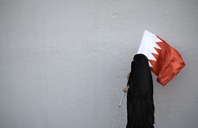 A woman holds the flag of Bahrain, a Shiite-majority Gulf kingdom