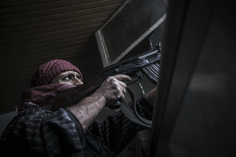 In this Wednesday, Oct. 24, 2012 photo, a Free Syrian Army sniper shoots his gun towards government troops as rebel fighters belonging to the Liwa Al Tawhid group carry out a military operation at the Moaskar front line, one of the battlefields in Karmal Jabl neighborhood, in Aleppo, Syria. (AP Photo/Narciso Contreras).
