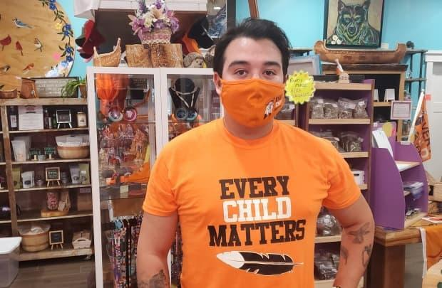 Wyler Diome-Montour displays a shirt that is available for sale at The Purple Dragonfly Trading Post in Kahnawake, where the store is thanking customers for supporting Indigenous initiatives. (Kwabena Oduro/CBC - image credit)