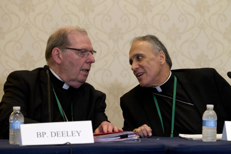 Bishop Robert Deeley of Portland Bishop of Diocese of Portland, left, speaks with Cardinal Daniel DiNardo of the Archdiocese of Galveston-Houston, speaks during a news conference at the United States Conference of Catholic Bishops (USCCB), 2019 Spring meetings in Baltimore, Md., Tuesday, Jun 11, 2019. (AP Photo/Jose Luis Magana)