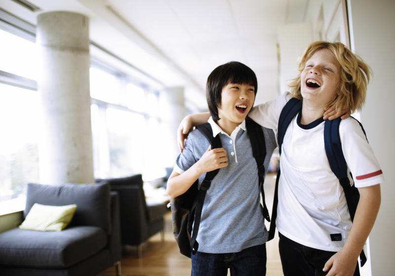 two boys laughing with arms around each other