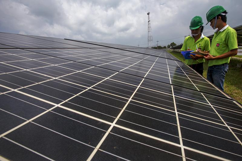 Employees of a solar farm company take notes between panels at the farm in Nakorn Ratchasima province, Thailand, October 3, 2013. Come December, Thailand will have more solar power capacity than all of Southeast Asia combined as record sums of money is poured into the sector in the hopes of nurturing a new energy source to help drive the region's second-biggest economy. To match story THAILAND-SOLAR/   Picture taken October 3, 2013. REUTERS/Athit Perawongmetha