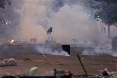 An anti-government protester runs through teargas during clashes in Caracas March 15, 2014. REUTERS/Jorge Silva