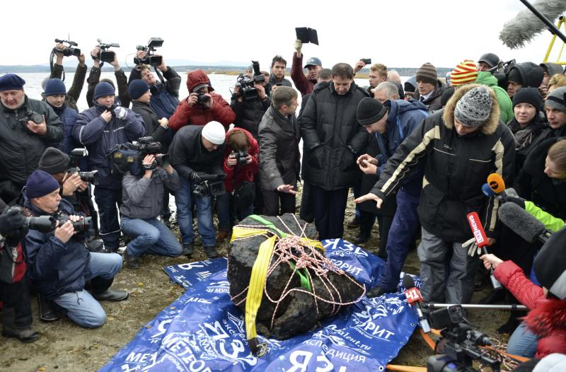 An object (C), which is a piece of a meteorite according to local authorities and scientists, is on display on the bank of the Chebarkul Lake, after it was lifted from the bottom of the lake, some 80 kilometers (50 miles) west of Chelyabinsk October 16, 2013. The meteorite exploded over central Russia in February 2013, raining fireballs over a vast area and causing a shock wave that smashed windows, damaged buildings and injured more than 1,000 people, according to local media. REUTERS/Anton Melnikov (RUSSIA - Tags: DISASTER SCIENCE TECHNOLOGY ENVIRONMENT)