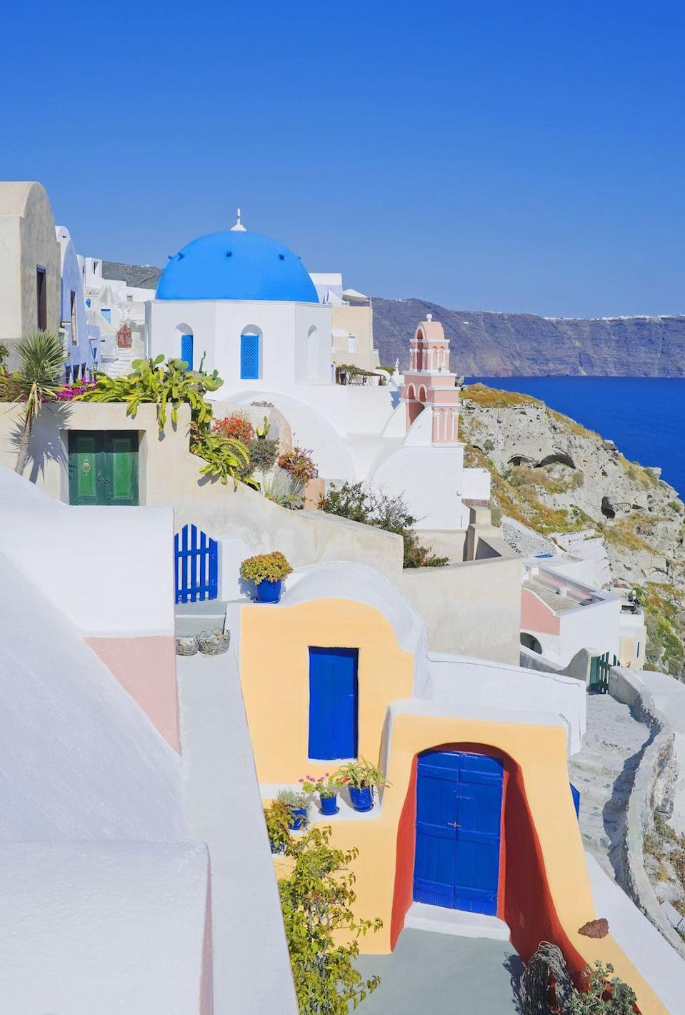 <p>A pop of Creamsicle orange is a pleasant surprise along the all-white streets of Santorini. </p>