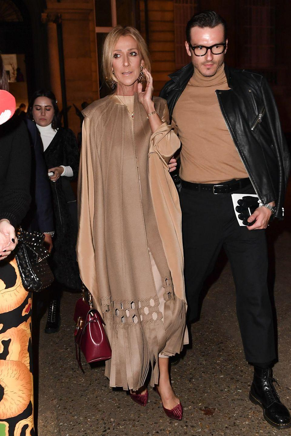 <p>Celine proves that beige doesn't have to be boring. At the Valentino fashion show, she wore a flowy cut-out overcoat with mauve pumps and a matching purse. She topped it off with gold accessories. </p>