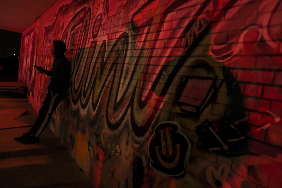 A student checks his phone as red and blue lights from a police vehicle reflect off a wall.