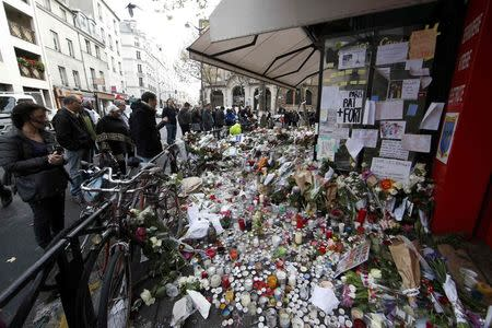 People look at flowers, candles and messages in tribute to victims in front of the La Belle Equipe cafe, one of the sites of the deadly attacks in Paris, France, November 17, 2015. REUTERS/Jacky Naegelen