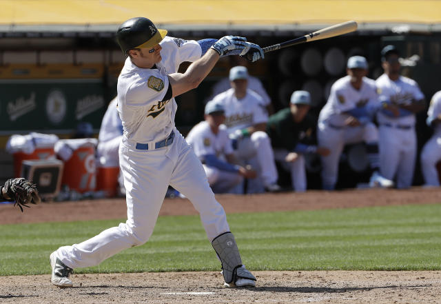 Oakland Athletics' Mark Canha hits an RBI-single against the Los Angeles Angels during the ninth inning of a baseball game in Oakland, Calif., Sunday, June 17, 2018. (AP Photo/Jeff Chiu)