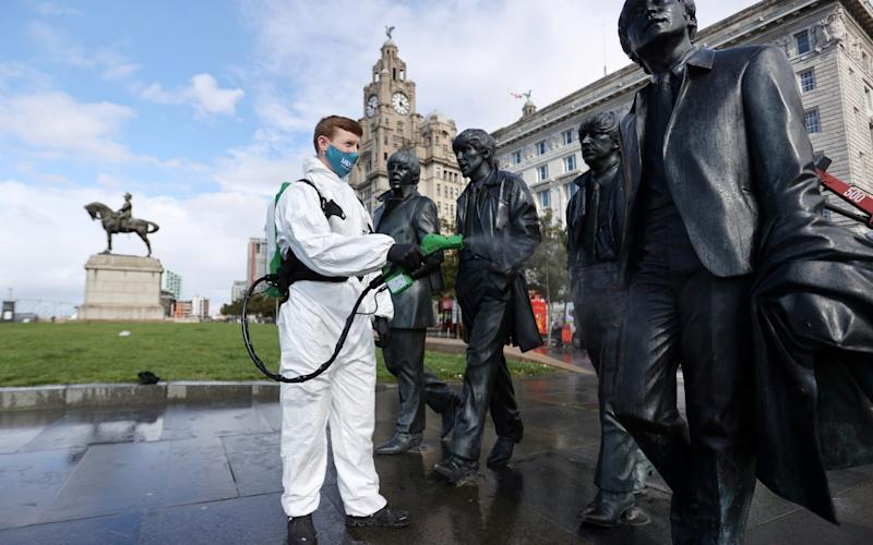 A man disinfects a statue of The Beatles in Liverpool - Reuters