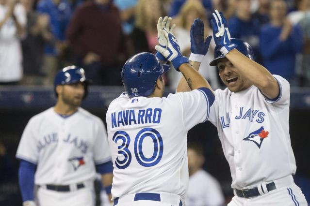 Toronto Blue Jays' Danny Valencia, right, celebrates with Dioner Navarro after hitting a three run homer off Boston Red Sox pitcher Junichi Tazawa during seventh inning American League baseball action in Toronto on Wednesday Aug. 27, 2014. (AP Photo/The Canadian Press, Chris Young)