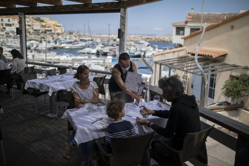FILE- In this Tuesday, June 2, 2020 file photo, diners apply hand sanitizer provided by staff at a seafood restaurant in Marseille, southern France. The coronavirus pandemic is gathering strength again in Europe and, with winter coming, its restaurant industry is struggling. The spring lockdowns were already devastating for many, and now a new set restrictions is dealing a second blow. Some governments have ordered restaurants closed; others have imposed restrictions curtailing how they operate. (AP Photo/Daniel Cole, File)