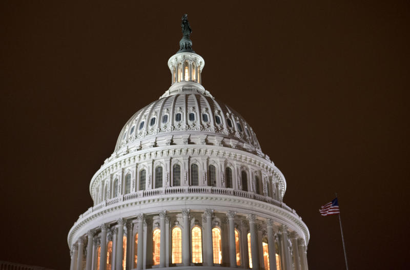 """As an evening haze lights the sky with a reddish glow, the lights of the U.S. Capitol burn into the night as the House continues to work on the """"fiscal cliff"""" legislation proposed by the Senate, in Washington, on Tuesday, Jan. 1, 2013. (AP Photo/Jacquelyn Martin)"""