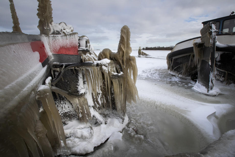 Icicles formed on boats after high winds and waves swept the marina of Monnickendam, Netherlands, Tuesday, Feb. 9, 2021. With freezing temperatures forecast for more than a week in the Netherlands, ice fever is sweeping the nation, offering a welcome respite from grim coronavirus news while also creating a challenge for authorities trying to uphold social distancing measures. (AP Photo/Peter Dejong)