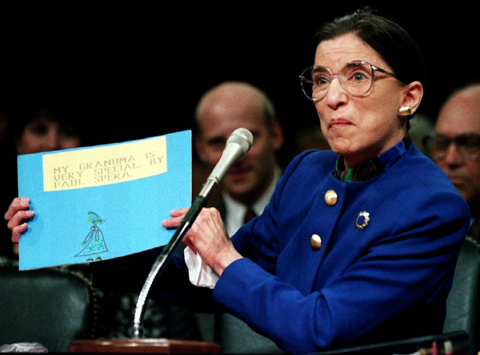 """US Supreme Court nominee Ruth Bader Ginsburg holds up a drawing of herself with the words """"My Grandmother Is Very Special by Paul Spera"""" as she appears before the Senate Judiciary Committee July 20, 1993, on Capitol Hill, on the first day of Ginsburg's confirmation hearings. Paul is Ginsburg's grandson."""