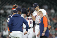 Houston Astros starting pitcher Jose Urquidy (65) removes his cap as he talks with manager Dusty Baker Jr., center left, before leaving the baseball game during the fourth inning against the Los Angeles Angels Wednesday, May 12, 2021, in Houston. (AP Photo/David J. Phillip)
