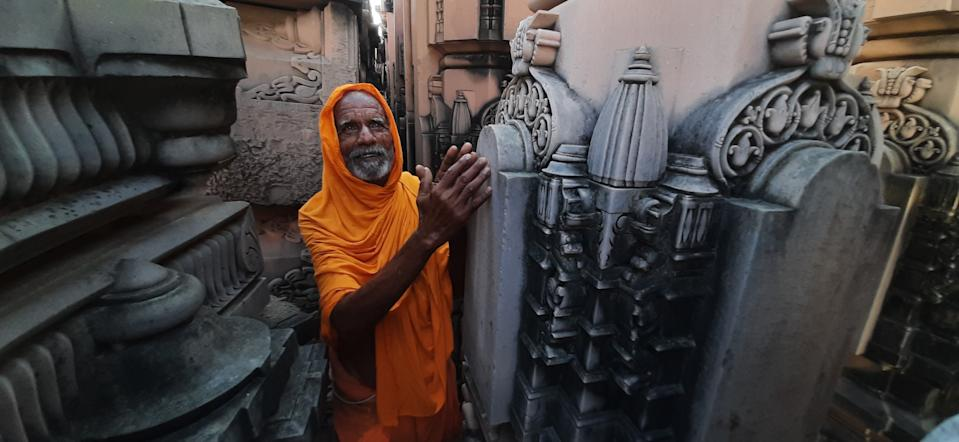 AYODHYA, INDIA - AUGUST 4: A sadhu in reverence next to stone pillars prepared for the Ram Janmabhoomi temple at the Ram Janm Bhoomi Nyas Karsevak Puram on August 4, 2020 in Ayodhya, India. Prime Minister Narendra Modi will on Wednesday attend a public function on laying of the foundation stone of 'Shree Ram Janmabhoomi Mandir' at Ayodhya. Ram Janmabhoomi Teerth Kshetra, the trust set up for the construction and management of Ram temple, has invited 175 eminent guests for the foundation stone-laying ceremony after personally discussing with BJP veterans L K Advani and Murli Manohar Joshi, lawyer K Parasaran and other dignitaries. (Photo by Deepak Gupta/Hindustan Times via Getty Images)