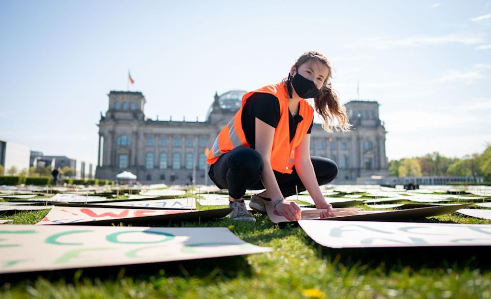 24 April 2020, Berlin: Luisa Neubauer of Fridays for Future lays out protest posters for the alternative climate strike on the Reichstag meadow. Because of the continuing spread of the corona virus, the climate strike is being digitally distributed on the Internet and strikers can participate via the website at www.fridaysforfuture.de/netzstreikfursklima. Photo: Kay Nietfeld/dpa (Photo by Kay Nietfeld/picture alliance via Getty Images)