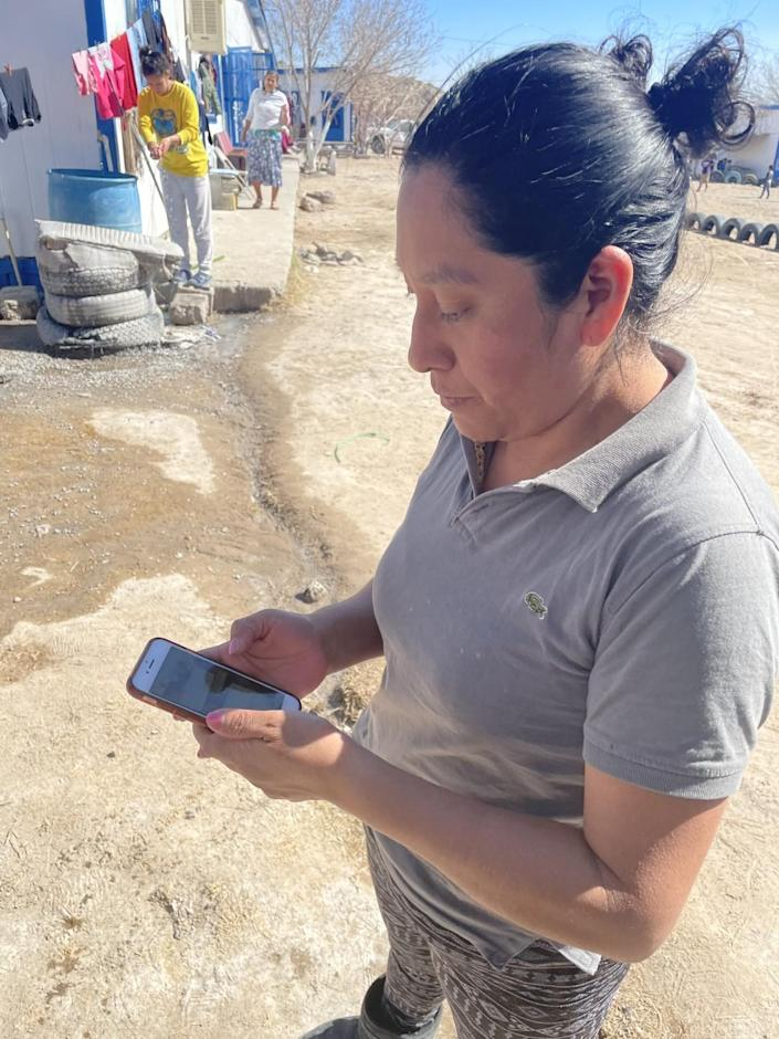 Angelina Baltazar uses her smartphone to try to enroll in new U.S. program for asylum seekers.