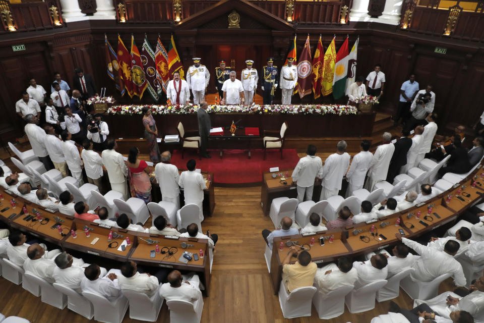 FILE- In this Nov. 22, 2019 file photo, Sri Lankan President Gotabaya Rajapaksa, center, stands during an oath-taking ceremony of his new cabinet members in Colombo, Sri Lanka. A proposed amendment to Sri Lanka's constitution that will consolidate powers in the President's hands has raised concerns about the independence of the country's institutions and the impact on its ethnic minorities who fear their rights could be undermined by the majoritarian will.(AP Photo/Eranga Jayawardena, File)