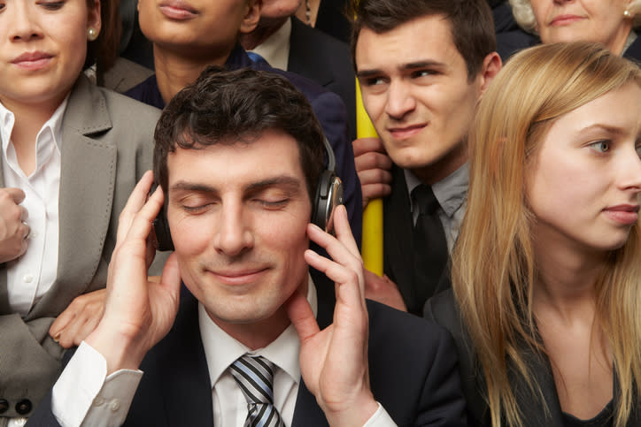 A man in a suit listening to his headphones on a crowded train.