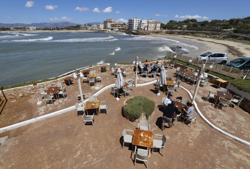 """11 May 2020, Spain, Palma: People sit on the terrace of the bar El Pe-on by the sea. From Monday, in """"Phase 1"""" of the relaxation of the corona measures, bars, restaurants, shops, libraries and religious places of worship, among others, will be allowed to reopen. Photo: Clara Margais/dpa (Photo by Clara Margais/picture alliance via Getty Images)"""