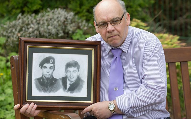 Karl Morris holding a picture of himself and his brother - Credit: Mark F Gibson/Caters