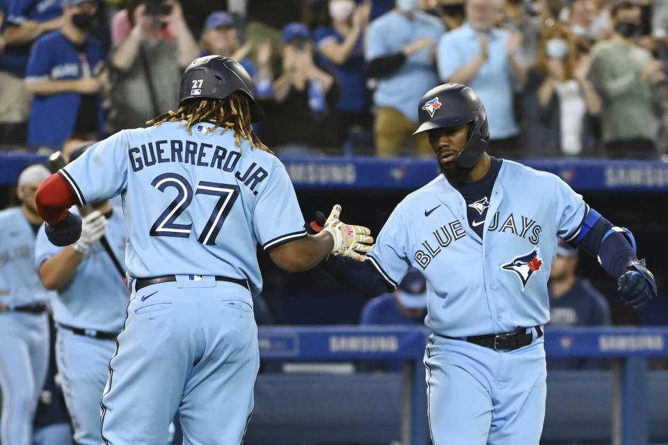 Toronto Blue Jays' Teoscar Hernandez, right, celebrates with Vladimir Guerrero Jr. (27) after hitting a two-run home run against the Oakland Athletics during the fourth inning of a baseball game Friday, Sept. 3, 2021, in Toronto. (Jon Blacker/The Canadian Press via AP