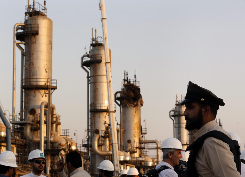 FILE - In this Sept. 20, 2019 file photo, a guard stands in front of Aramco's oil processing facility after the Sept. 14, 2019, attack on Aramco's oil processing facility in Abqaiq, near Dammam in the Kingdom's Eastern Province. A small instrument that two reports say was found inside drones which targeted the heart of Saudi Arabia's oil industry and those in the arsenal of Yemen's Houthi rebels, matches components recovered in downed Iranian drones in Afghanistan and Iraq. Conflict Armament Research said in a report released on Wednesday, Feb. 19, 2020, that these gyroscopes within the drones have only been found inside those manufactured by Iran. (AP Photo/Amr Nabil, File)