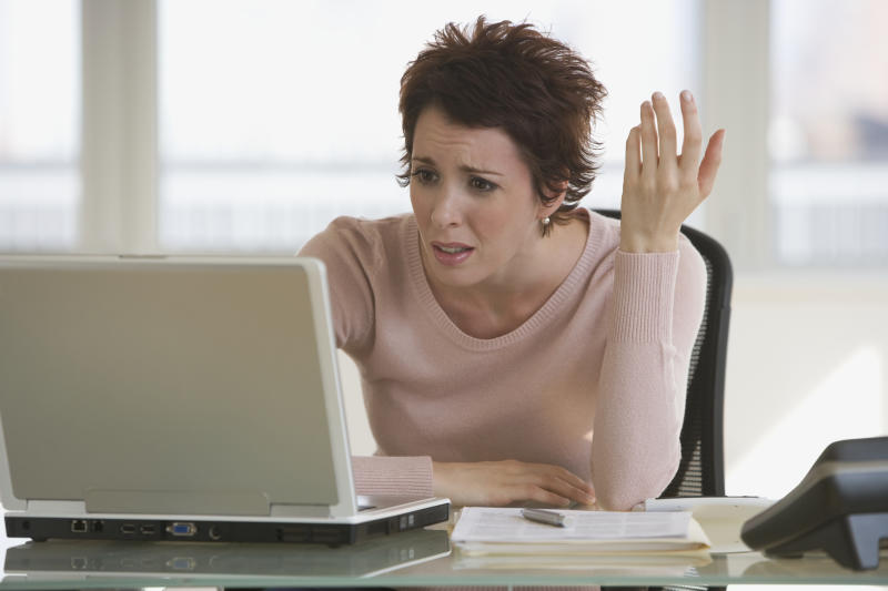 Frustrated businesswoman looking at laptop