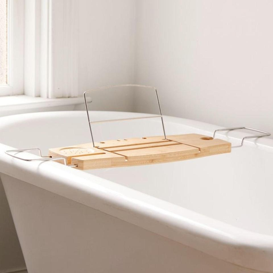 """This bamboo caddy is easy to store, extends to fit any size tub, and serves as a home for anything you need on hand—wine and TikTok included. $49, Urban Outfitters. <a href=""""https://www.urbanoutfitters.com/shop/me-time-bamboo-bath-tray-caddy?"""" rel=""""nofollow noopener"""" target=""""_blank"""" data-ylk=""""slk:Get it now!"""" class=""""link rapid-noclick-resp"""">Get it now!</a>"""