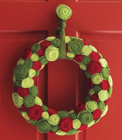 """<p>Who says roses are only for the spring? In this festive holiday wreath however, you can use colorful felt to create """"roses"""" suitable for all your Christmas decorating needs.</p><p><strong><em><a href=""""https://www.womansday.com/home/crafts-projects/how-to/a6322/craft-how-to-ring-of-roses/"""" rel=""""nofollow noopener"""" target=""""_blank"""" data-ylk=""""slk:Get the Ring of Roses holiday wreath tutorial."""" class=""""link rapid-noclick-resp"""">Get the Ring of Roses holiday wreath tutorial.</a></em></strong></p>"""