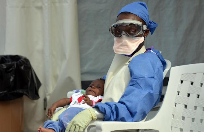 A Liberian health worker holds a baby infected with the Ebola virus on October 18, 2014 at an Ebola treatment centre in Monrovia (AFP Photo/Zoom Dosso)