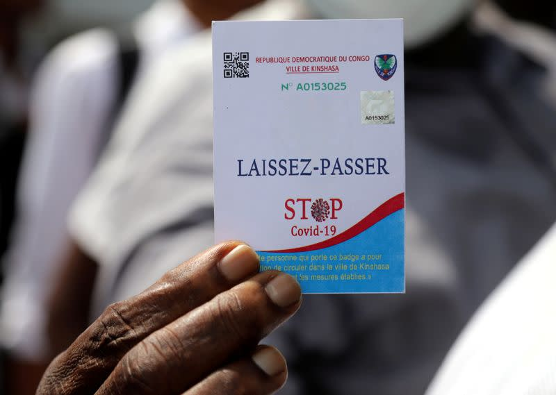 FILE PHOTO: A Congolese civilian displays his laissez-passer card during a total lockdown amid concerns about the spread of the coronavirus disease (COVID-19), in Gombe commune of Kinshasa