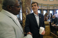 Republican Sen. Briggs Hopson, of Vicksburg, right, is congratulated by Sen. John Horhn, D-Jackson, for successfully navigating a resolution to suspend the rules and vote to change the state flag Saturday, June 27, 2020, at the Capitol in Jackson, Miss. The resolution passed and now the House and Senate are expected to pass a bill that removes the current flag and establishes a path forward to getting a new one. Gov. Tate Reeves has already said he would sign whatever flag bill the Legislature decides on. The current flag has in the canton portion of the banner the design of the Civil War-era Confederate battle flag, that has been the center of a long-simmering debate about its removal or replacement. (AP Photo/Rogelio V. Solis)