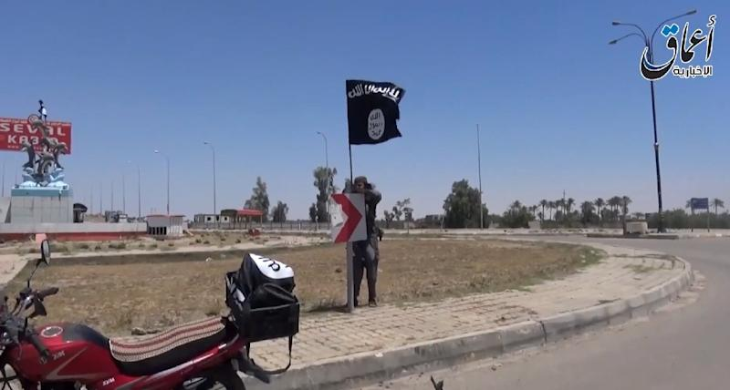 An image grab taken from a video uploaded on May 18, 2015 by Aamaq News Agency allegedly shows an IS fighter hanging a flag of the group in a street of Ramadi