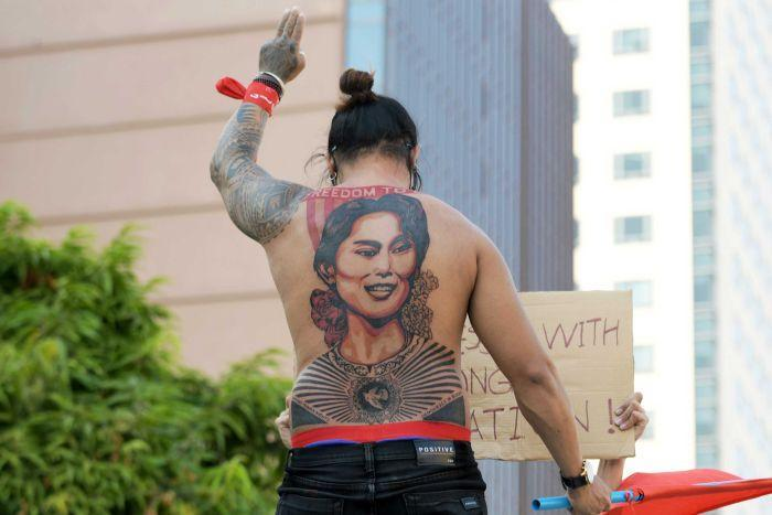 A man with a tattoo of Aung San Suu Kyi holds up a three-finger salute.
