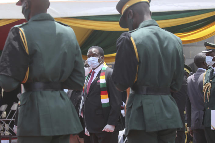 """Zimbabwe President Emmerson Mnangagwa attends the burial of Dr Ellen Gwaradzimba who died of COVID-19, at the Heroes Acre in Harare, Thursday, Jan. 21, 2021. Zimbabwean President Emmerson Mnangagwa who presided over the burial called the pandemic """"evil"""" and urged people to wear masks, practice social distancing and sanitize, as cases across the country increased amid a fragile health system. (AP Photo/Tsvangirayi Mukwazhi)"""