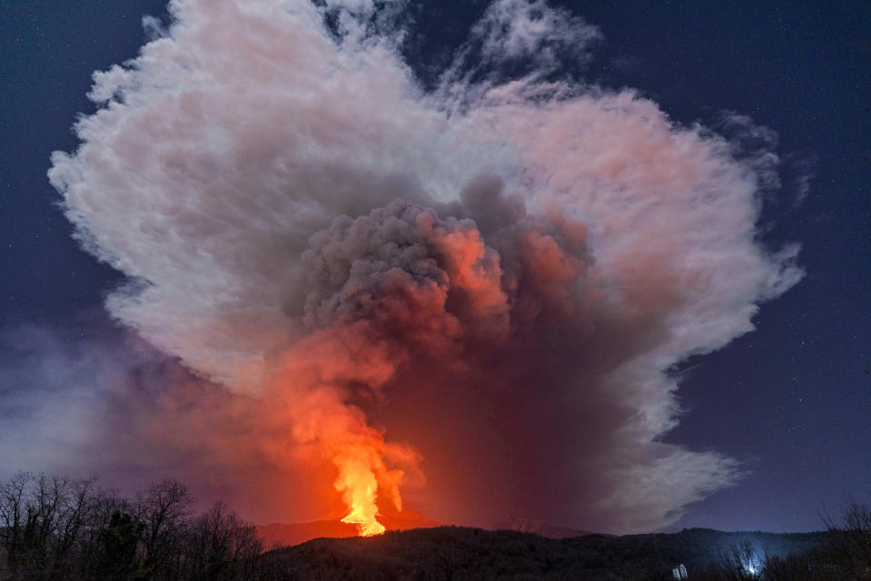 A fiery river of glowing lava flows on the north-east side of the Mt Etna volcano engulfed with ashes and smoke near Milo, Sicily, Wednesday night, Feb. 24, 2021. Europe's most active volcano has been steadily erupting since last week, belching smoke, ash, and fountains of red-hot lava. (AP Photo/Salvatore Allegra)