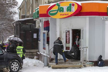 Investigators carry the body of a victim, killed by a grenade blast in a shop, in central Chisinau