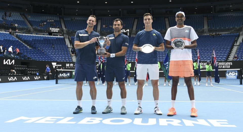 Four men stand on a tennis court at the Australian Open with vacant stadium seen in the background
