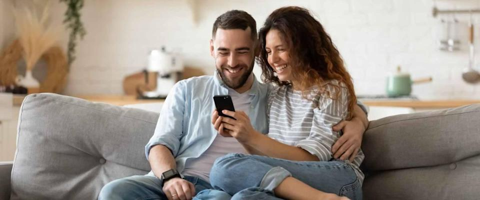 Happy young wife showing cellphone to laughing husband.