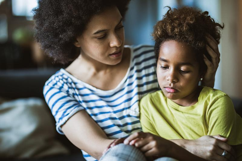 Young black mother taking care of her depressed little daughter at home.