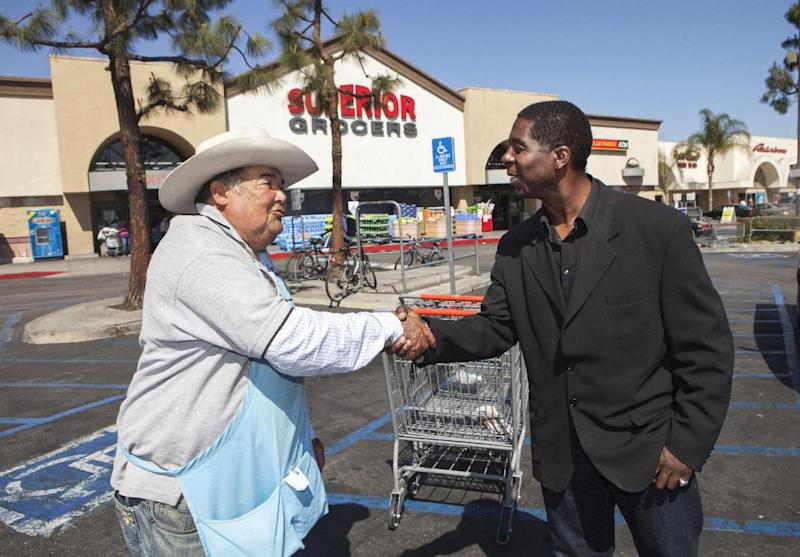 In this photo taken Wednesday, Mar. 13, 2013, former child actor Rodney Allen Rippy poses for a photo with an unidentified supporter, near Compton City Hall in Compton, Calif. Rippy is running for Mayor of Compton in the upcoming April election. (AP Photo/Damian Dovarganes)