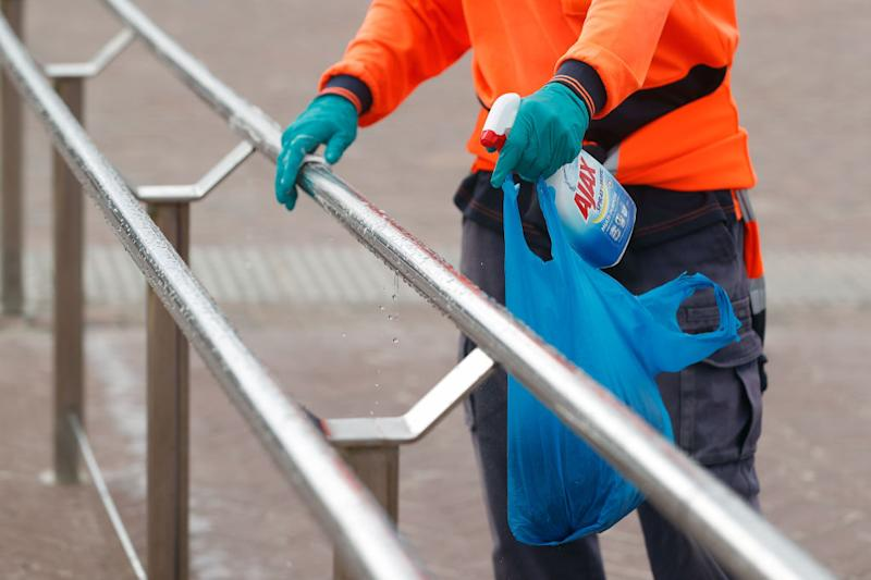 A council worker cleans handrails with disinfectant at Bondi Beach in Sydney.
