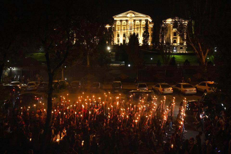 Torchlight procession march during a demonstration to mark the 106th anniversary of the massacre and honors the victims of Armenian Genocide, with the Government buildings in the background in Yerevan, Armenia, Saturday, April 24, 2021. Armenians marked the anniversary of the death of up to 1.5 million Armenians by Ottoman Turks, an event widely viewed by scholars as genocide, though Turkey refutes the claim. (Grigor Yepremyan/PAN Photo via AP)