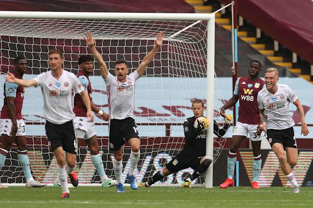 Sheffield United's players appeal to referee Michael Oliver after what should've been the first Premier League goal since March. (Carl Recine/Getty Images)