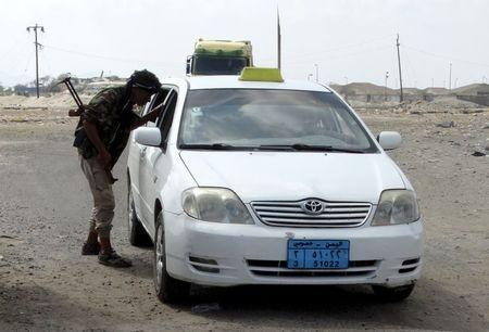 Member of the pro-government Popular Committees militia inspects a car at a checkpoint on a road leading to Yemen'a southern province of Abyan