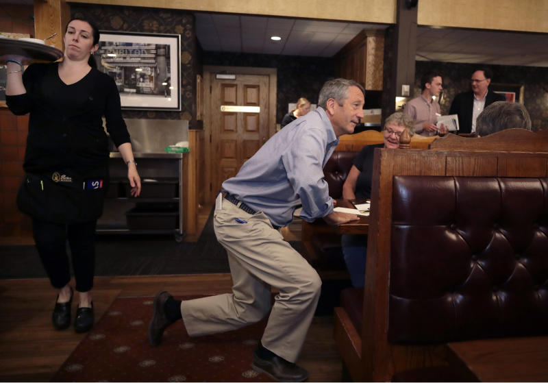 Republican presidential candidate, former South Carolina Gov. Mark Sanford kneels to talk with customers at the Puritan Backroom restaurant, during a campaign stop, Thursday, Sept. 19, 2019, in Manchester, N.H. (AP Photo/Elise Amendola)